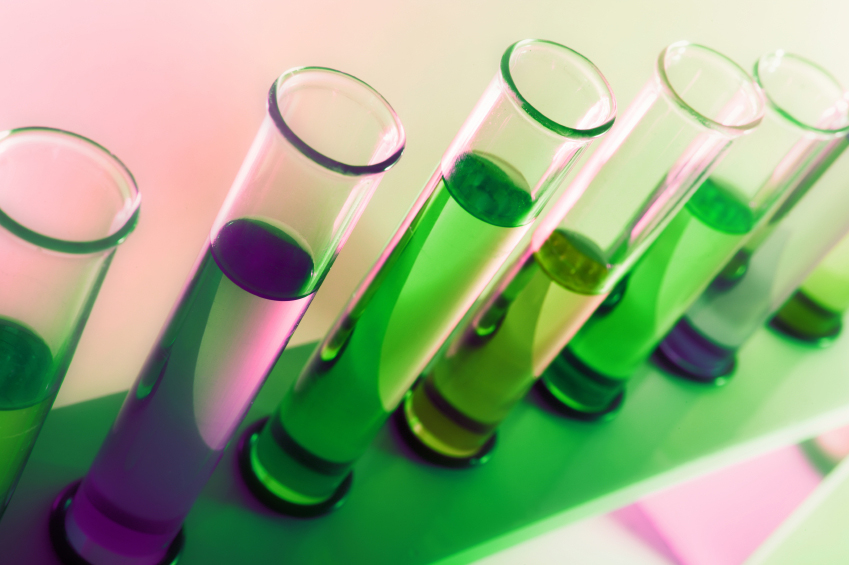 Laboratory test tubes filled with clear liquid and sitting in a rack lit with green and purple lights