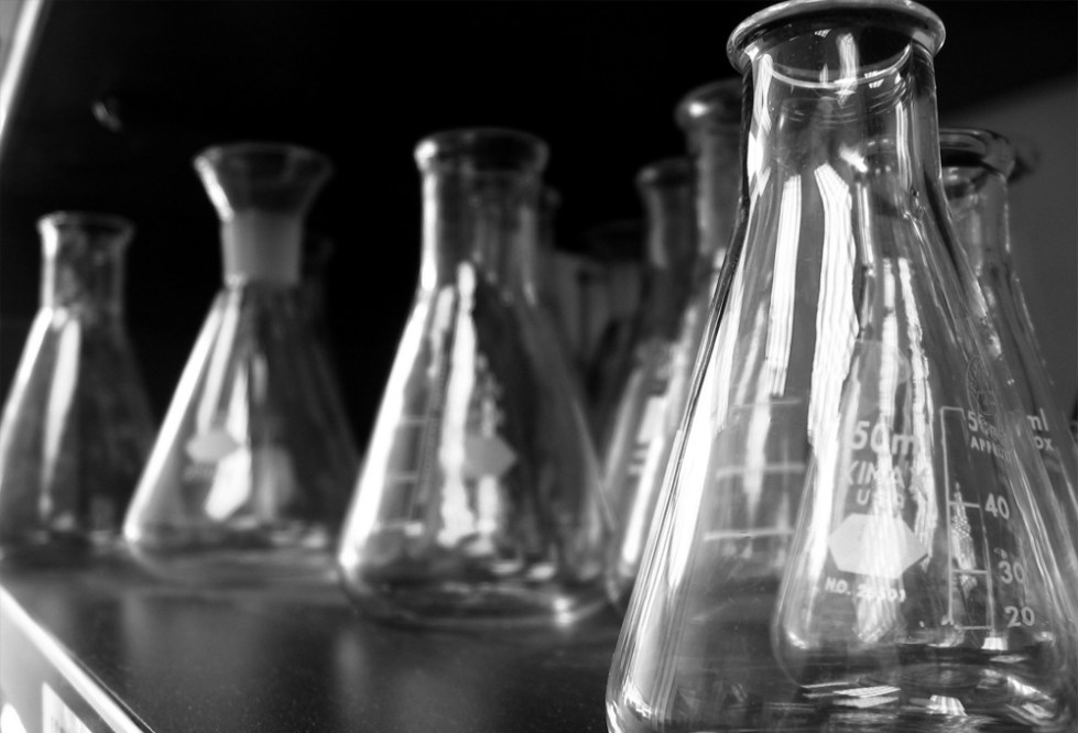 Black and white photo of clear glass lab beakers on a table