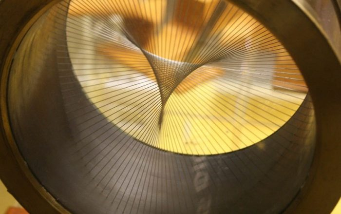 Image of a yellow and gold metal circle with wires across the center, in an abstract geometic pattern.