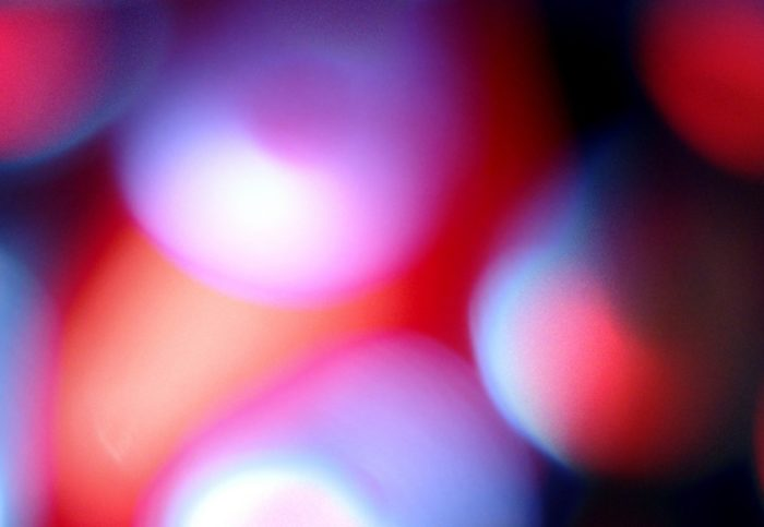 Abstract image of round and oval shapes in reds, pinks, whites, and light blues