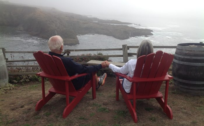 Marc Binder, a pancreatic cancer survivor, and his wife sit in red Adirondack chairs overlooking water and more land