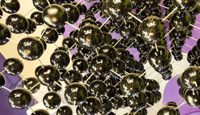 metal balls connected with thin sticks on a purple and white background