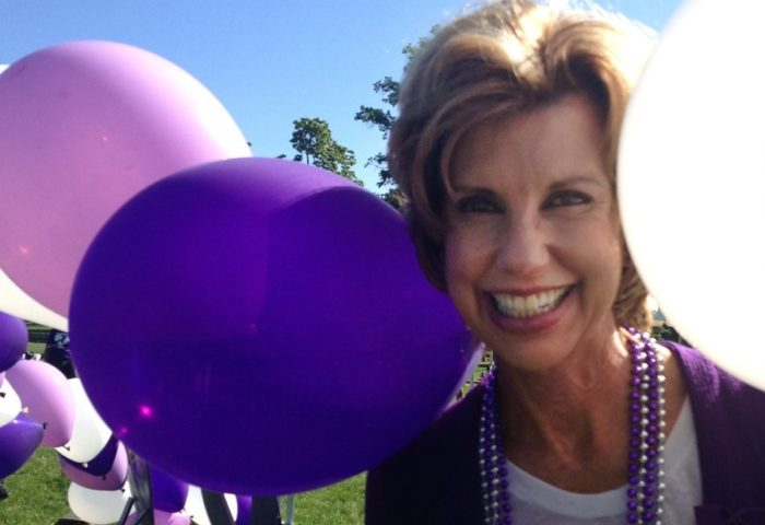 Long-term pancreatic cancer survivor Laurie MacCaskill surrounded by purple and white balloons