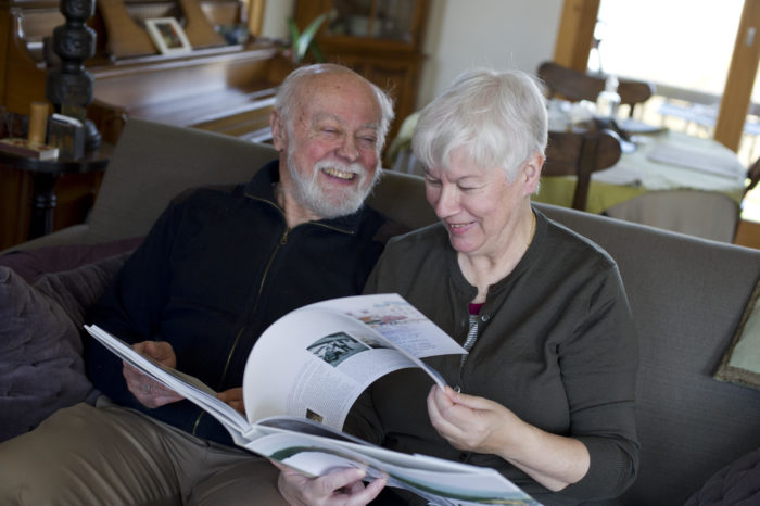Brigitte Regnier and her husband read a book together while seated on a sofa.