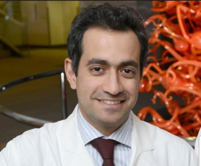 Dr. Shalaan Beg, pancreatic cancer researcher, standing in a hallway.