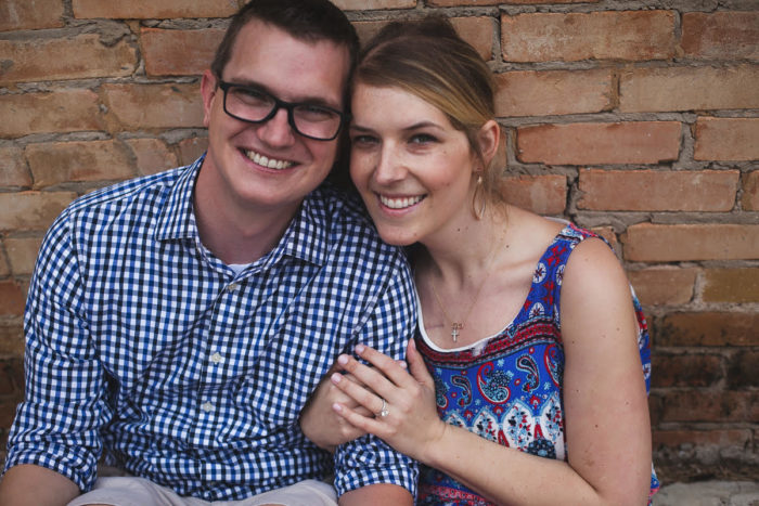 Allison Lippman and Eric Kuban in their engagement photo, against a brick background.