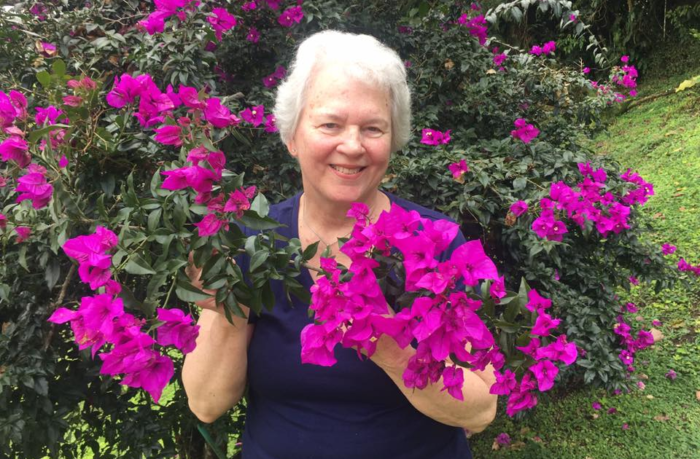 Pancreatic cancer patient Miriam Hermosa surrounded by purple flowers