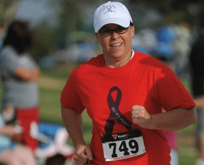 Pancreatic neuroendocrine tumor survivor Kristin Sine in a dark orange shirt and white ball cap running a race.