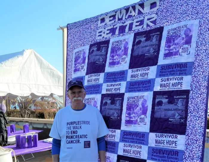 Pancreatic cancer survivor John O'Grady standing in front of a purple and white quilt he made