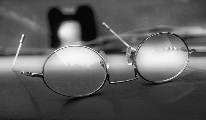 Black and white image of fogged glasses on a desk