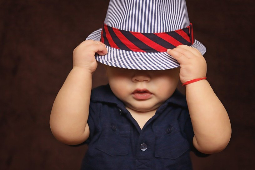 baby boy in blue shirt covered with a striped blue hat with red and blue trim