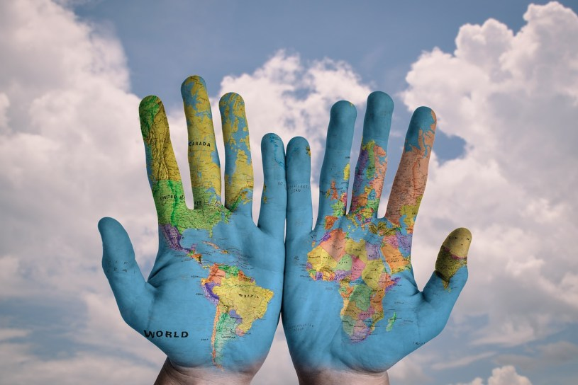 hands painted with the globe against a cloud filled sky