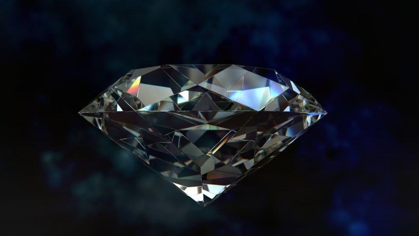 large faceted crystal cut diamond against a dark blue blurred background