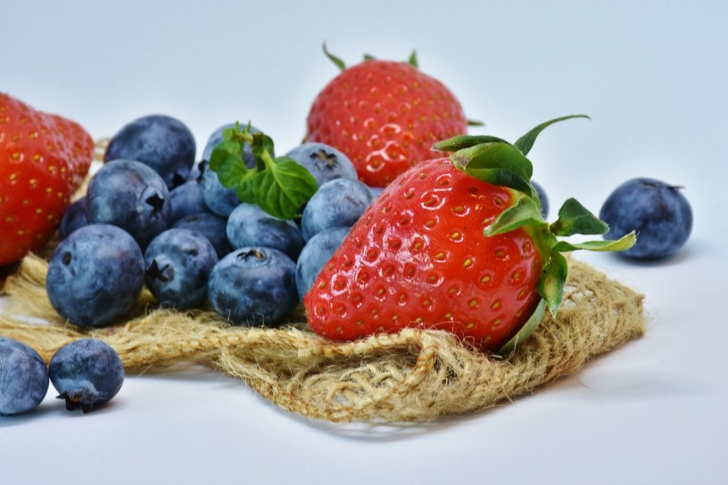 strawberries and blueberries sitting on burlap