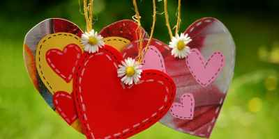 three whimsical hearts on strings dangling in the wind