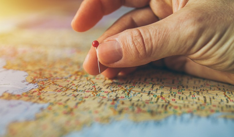 travel: hand placing a red balled pin on top of a map location