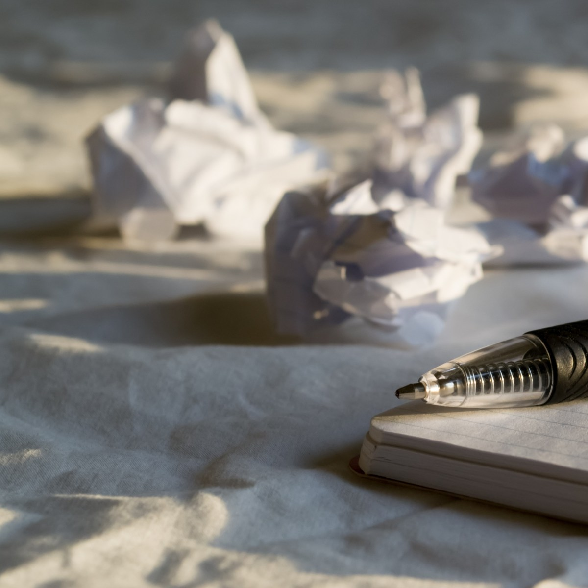 pen and paper and crumbled paper wads