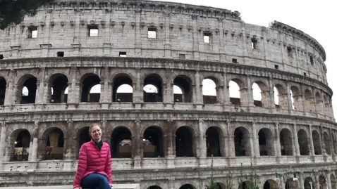 Girl sitting in front of the colosseum