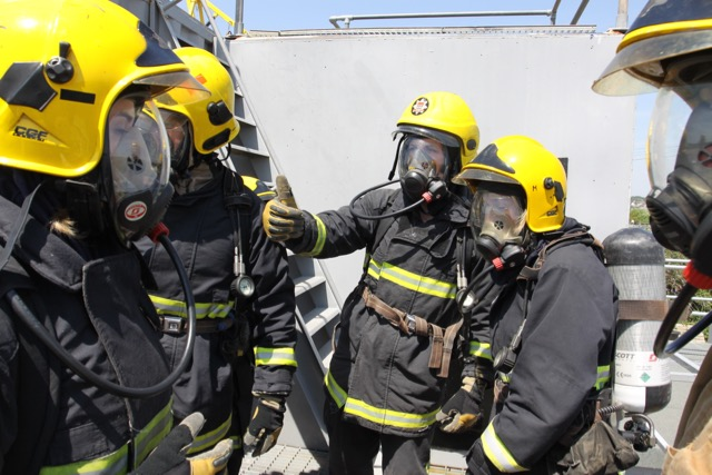 a group of people standing around in firefighting gear for the STCW course