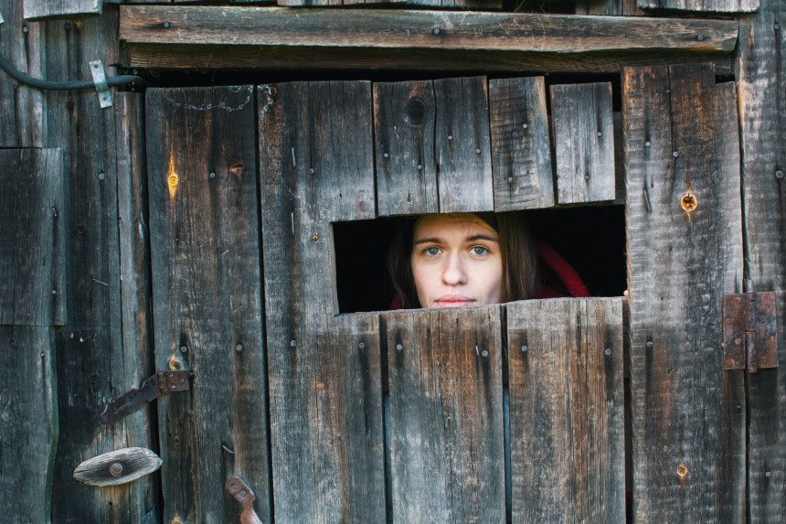 Young woman looking through the crack of a locked wooden shed.