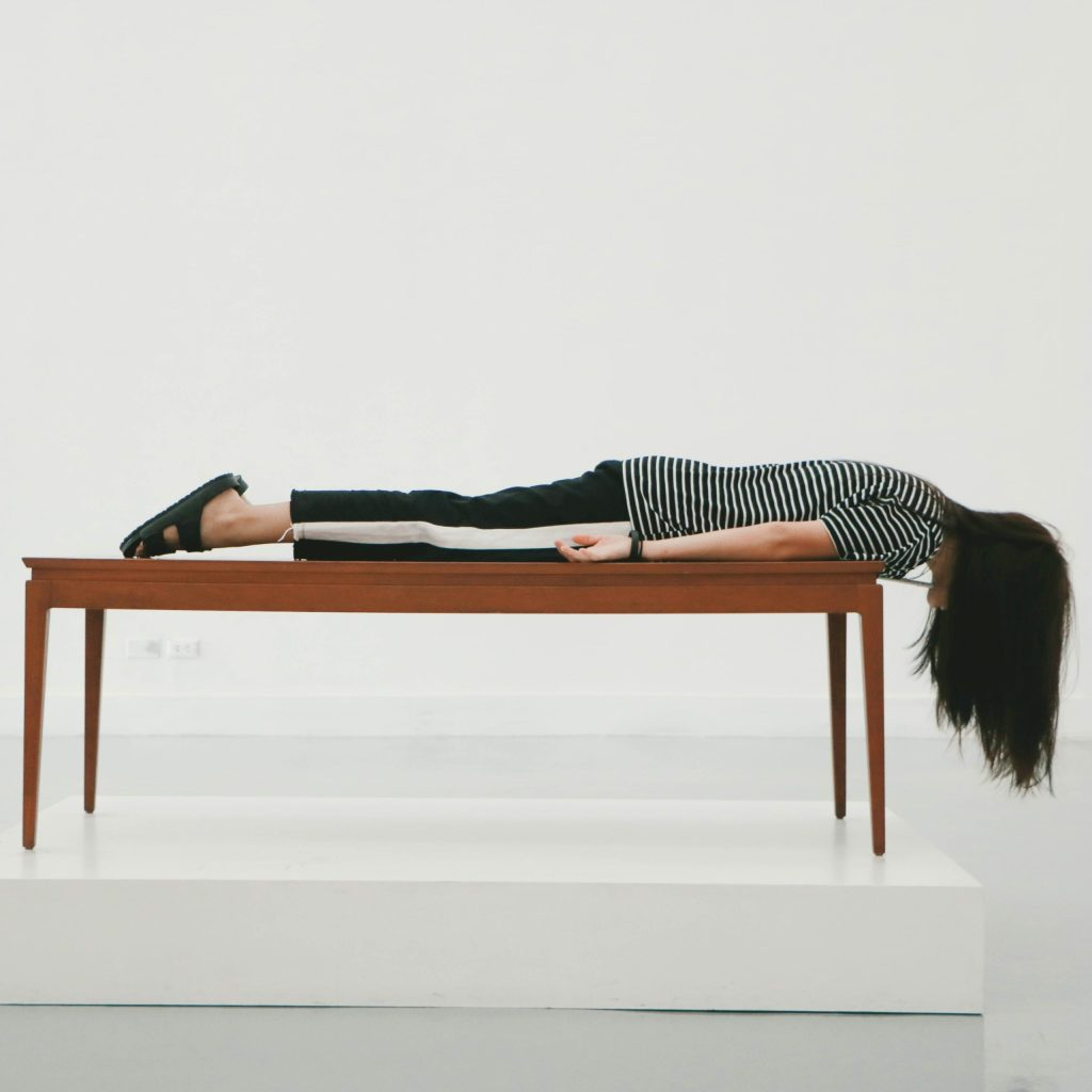 A woman planking on a bench is overwhelmed by decluttering.