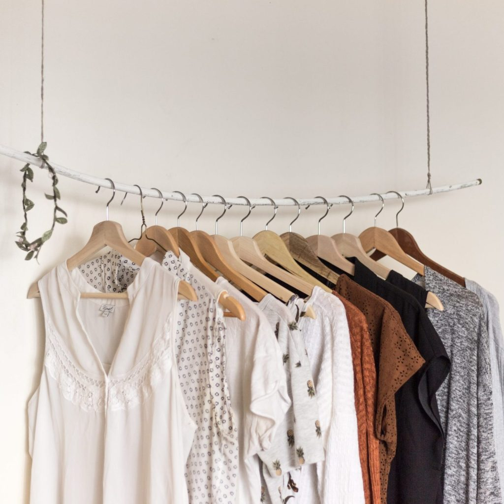 clothes are hanging on a rack as a clever storage solution for tiny living