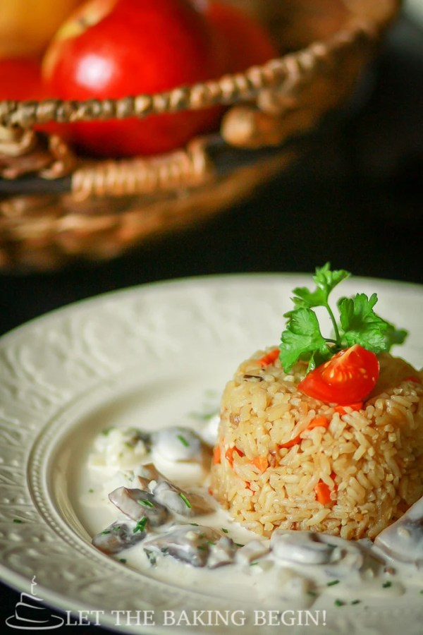 Fried rice topped with fresh greens and tomatoes on a white decorative bowl with mushroom sauce.