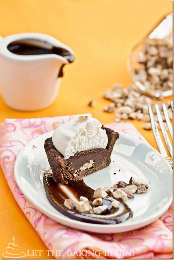 Salted Caramel Ganache & Hazelnut Chantilly Cream Tartlet on a plate with chocolate drizzle.
