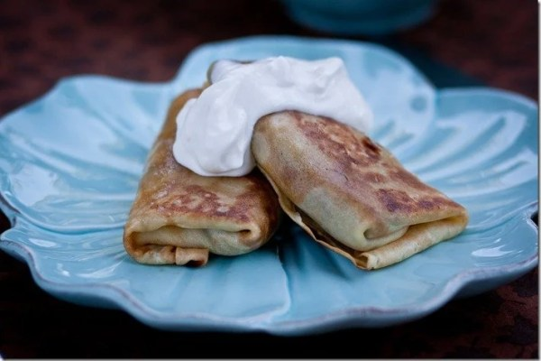 Two crepes filled with meat topped with sour cream on a decorative blue plate.