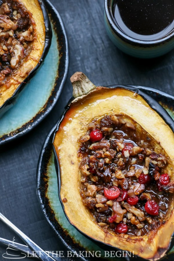 Top view picture of stuffed acorn squash next to spoons and a cup of coffee.