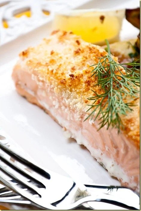 Side view of parmesan crusted salmon topped with fresh greens on a white plate with fresh lemons.
