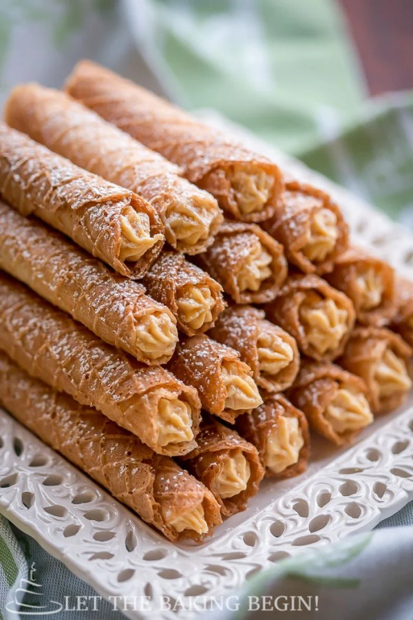 Stacked crispy wafers sprinkled with powdered sugar on a white decorative tray.