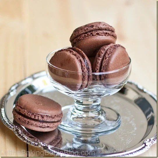 Dark Chocolate Truffle Macarons in a cup with one on a tray.