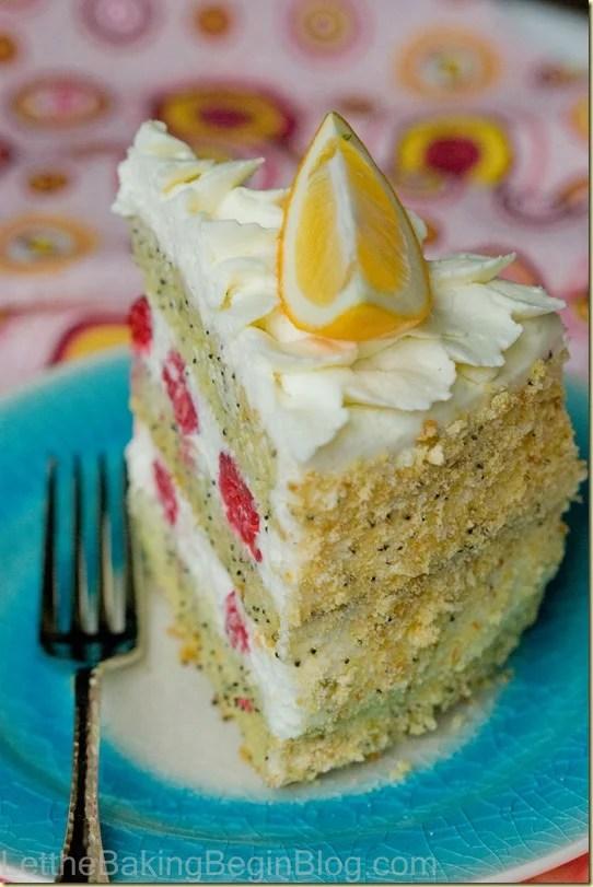 Poppy seed lemon cake slice topped with a lemon on a blue decorative plate.