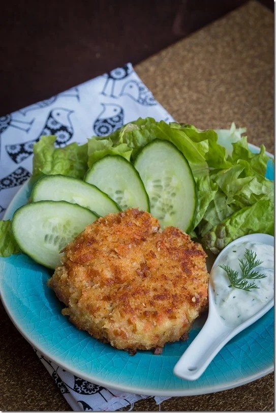 Salmon cake with tzatziki sauce on a decorative plate with cucumbers and romaine.