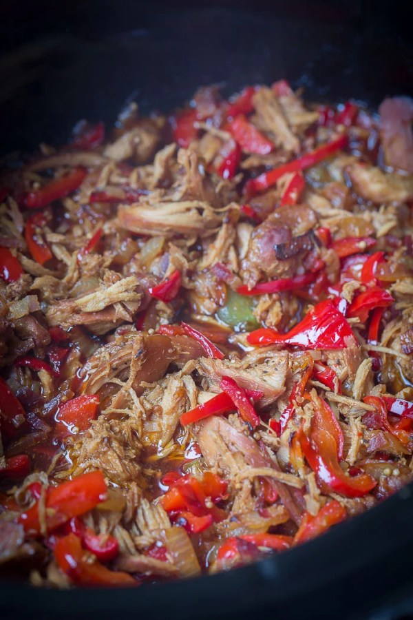Close up picture of chicken in crockpot with peppers.