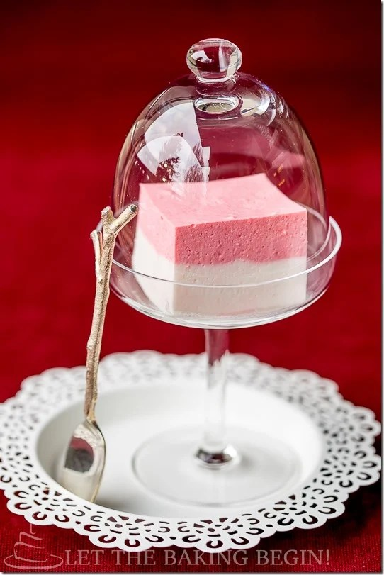 Strawberry jello in a glass with cover on a white decorative plate with a wooden spoon.