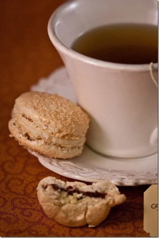 Rafaello macaron on a plate next to a cup of tea.