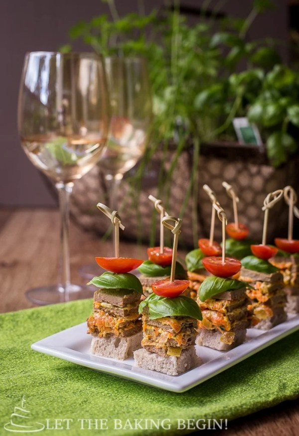 Chicken stacks with tomatoes on a decorative white plate on a green napkin.