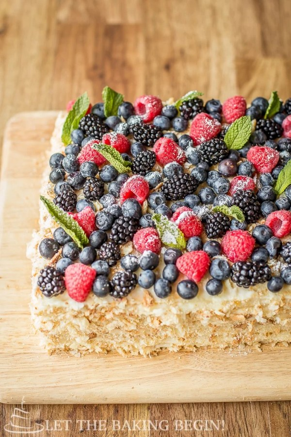 Cake topped with blueberries, raspberries, blackberries, blueberries, mint, and powdered sugar on a wooden cutting board.