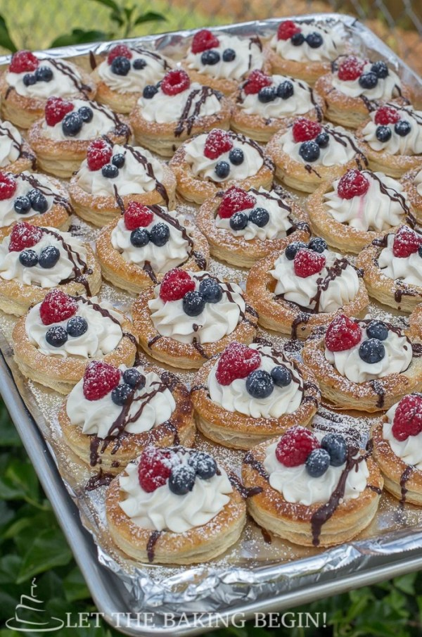 Puff pastry berries and cream tarts on a baking sheet sprinkled with powdered sugar and chocolate drizzle.