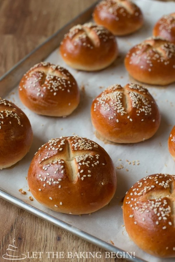Buns topped with sesame seeds laid out on a parchment lined baking sheet.