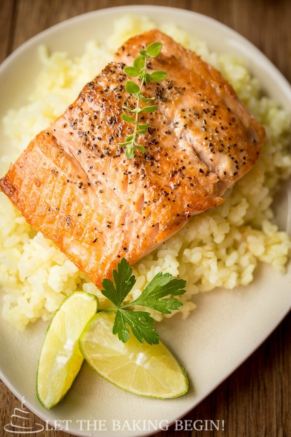 Pan seared salmon on top of a bed or rice with with limes next to it.