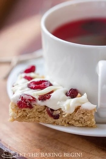 Cranberry bliss bar on a white decorative plate with a cup of tea in a white mug.