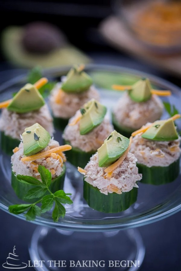 Seven cucumber tuna bites topped with cheese and avocado on a glass platter topped with fresh greens.