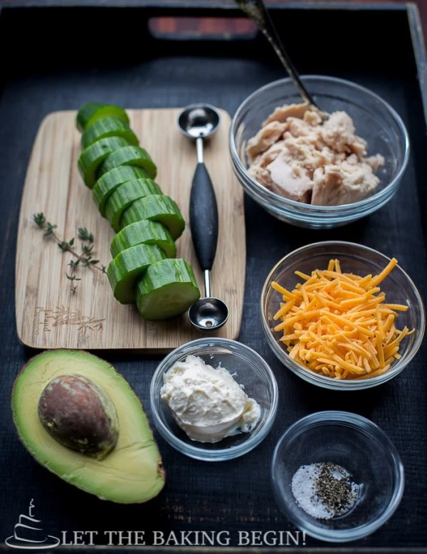Sliced cucumbers, bowl of tuna, bow of cheese, a bowl of salt and pepper, bowl of mayonnaise, chopped greens, melon scooper and avocado displayed in a wooden tray.
