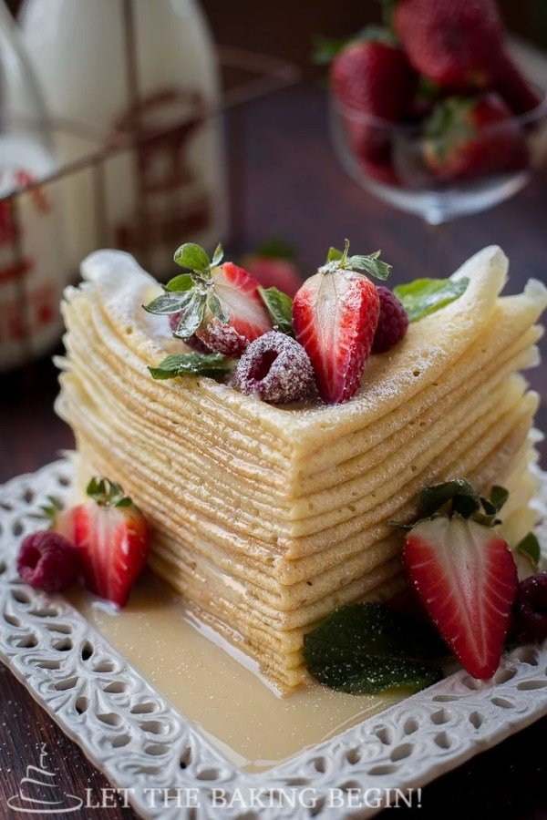 Buttermilk crepes stacked on top of each other topped with fresh strawberries and raspberries.