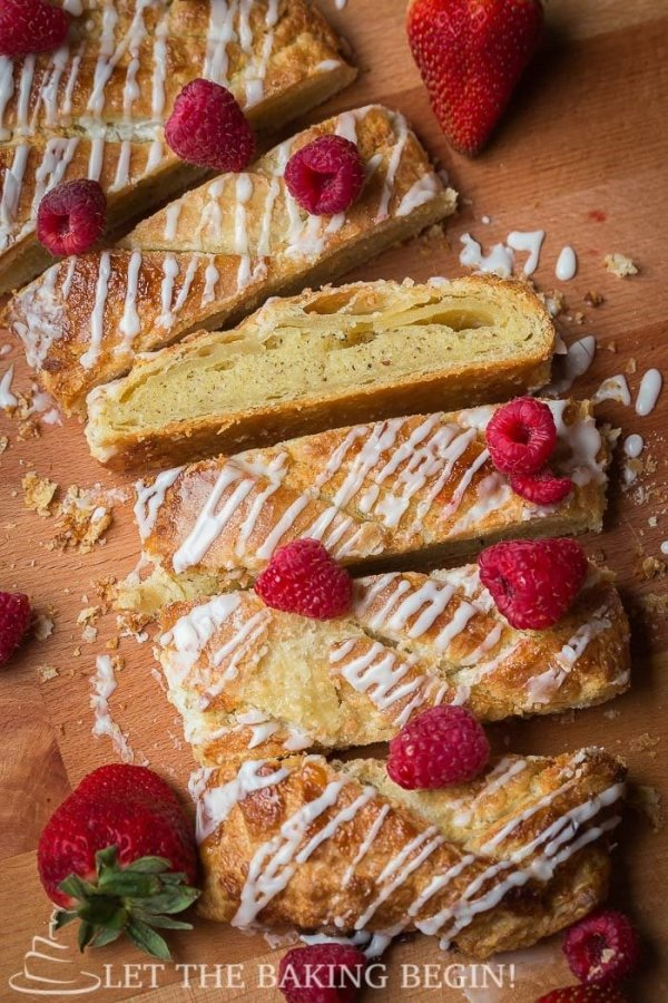 Sliced puff pastry braid topped with powdered sugar glaze and raspberries.