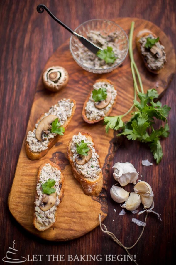Mushroom pate spred over toasted baguettes all lying on a wooden cutting board.