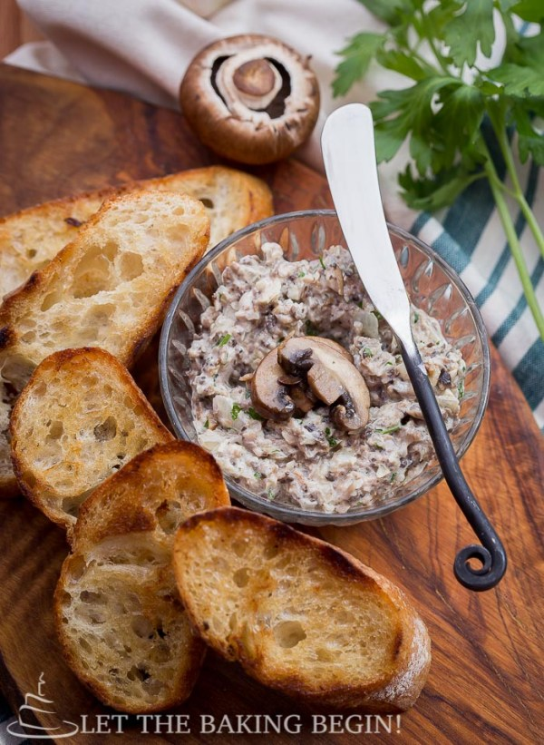 Mushroom pate in a glass bowl with toasted baguette slices next to it